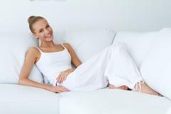 Mujer atractiva feliz que se inclina en el sofá blanco Fotografía de archivo libre de regalías