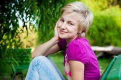 Mujer atractiva feliz que se sienta en banco en parque Foto de archivo