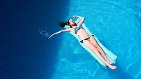 Mujer atractiva Flotador milenario de la muchacha en la piscina, festival, hotel, playa, evento que sonríe con las gafas de sol e almacen de video