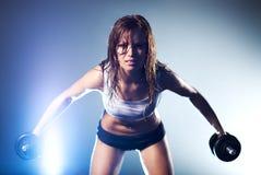 Mujer atractiva fuerte joven con pesas de gimnasia Imagen de archivo