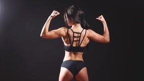 Mujer atractiva fuerte joven que muestra sus músculos metrajes