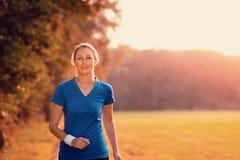 Mujer atractiva hacia fuera que ejercita en luz que brilla intensamente foto de archivo