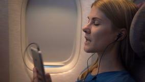 Mujer atractiva hermosa cerca de la ventana del aeroplano Vuelo de larga distancia Escuche la música en smartphone almacen de video