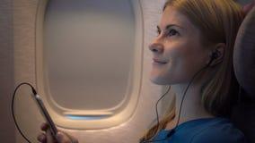Mujer atractiva hermosa cerca de la ventana del aeroplano Vuelo de larga distancia Escuche la música en smartphone metrajes