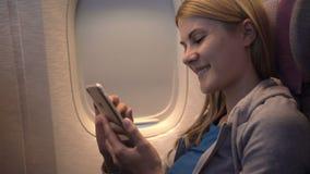 Mujer atractiva hermosa cerca de la ventana del aeroplano Vuelo de larga distancia Usando el smartphone, hojeando almacen de metraje de vídeo