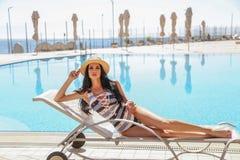 Mujer atractiva hermosa con el pelo oscuro en el traje que nada elegante que presenta cerca de piscina al aire libre fotos de archivo
