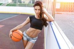 Mujer atractiva hermosa con el pelo que agita que juega outgoor del baloncesto Fotos de archivo libres de regalías