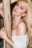 Mujer atractiva hermosa con el pelo rubio rizado largo, los ojos verdes bastante dulces y los labios llenos atractivos en el oest Foto de archivo libre de regalías