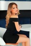 Mujer atractiva hermosa con el vestido negro y el pelo rubio que se sientan en la tabla Muchacha de la manera Fotos de archivo libres de regalías