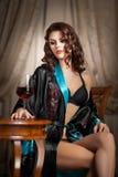 Mujer atractiva hermosa con el vidrio de vino que se sienta en silla. Retrato de una mujer con el pelo rizado largo que plantea de Foto de archivo