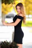 Mujer atractiva hermosa con la presentación del vestido negro y del pelo rubio al aire libre Muchacha de la manera Foto de archivo libre de regalías