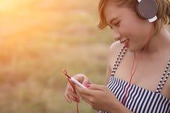 Mujer atractiva hermosa con música que escucha permanente del vestido azul adentro Fotografía de archivo