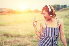 Mujer atractiva hermosa con música que escucha permanente del vestido azul adentro Imagenes de archivo