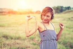 Mujer atractiva hermosa con música que escucha permanente del vestido azul adentro Imagen de archivo libre de regalías