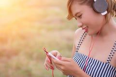 Mujer atractiva hermosa con música que escucha permanente del vestido azul adentro Foto de archivo libre de regalías