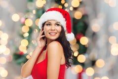 Mujer atractiva hermosa en el sombrero de santa y el vestido rojo Foto de archivo libre de regalías