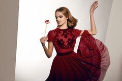 Mujer atractiva hermosa en el vestido de seda con los labios del caramelo en el palillo Imagen de archivo libre de regalías