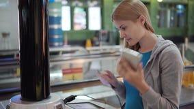Mujer atractiva hermosa en terminal de aeropuerto Soporte de carga cercano derecho pluging en smartphone almacen de video