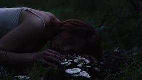 Mujer atractiva hermosa joven en endecha p?rpura de la falda en un toc?n con las setas blancas en el bosque crepuscular misterios almacen de metraje de vídeo