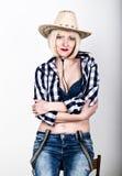 Mujer atractiva hermosa joven en vaqueros de la camisa de tela escocesa y un sombrero de vaquero Imagen de archivo