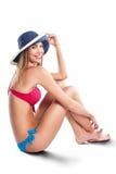 Mujer atractiva hermosa joven que presenta en la playa y que mira el mar Foto de archivo libre de regalías