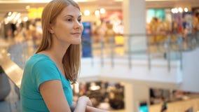 Mujer atractiva hermosa joven que se coloca en la alameda de compras, sonriendo Concepto del consumerismo de las compras almacen de video