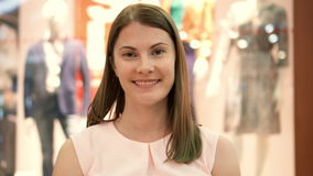 Mujer atractiva hermosa joven que se coloca en la alameda de compras, sonriendo Concepto del consumerismo de las compras metrajes