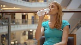 Mujer atractiva hermosa joven que se sienta en agua potable del café de la alameda de compras de la botella plástica metrajes