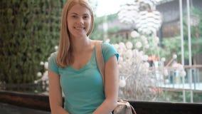 Mujer atractiva hermosa joven que se sienta en la alameda de compras, sonriendo Concepto del consumerismo de las compras almacen de video