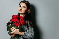 Mujer atractiva hermosa joven que sostiene el ramo de rosas rojas g imagen de archivo libre de regalías