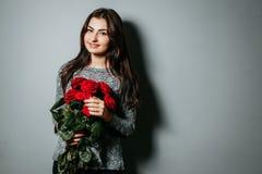Mujer atractiva hermosa joven que sostiene el ramo de rosas rojas g imagenes de archivo