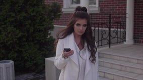 Mujer atractiva hermosa joven que usa su teléfono móvil HD al aire libre metrajes