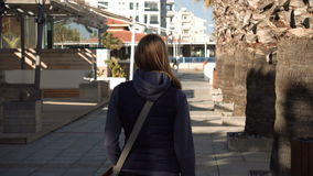 Mujer atractiva hermosa que camina abajo de la calle, sol, sombras De detrás De centro turístico de la estación almacen de metraje de vídeo
