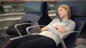 Mujer atractiva hermosa que duerme en terminal de aeropuerto Jet lag conectado distancia de los vuelos almacen de video