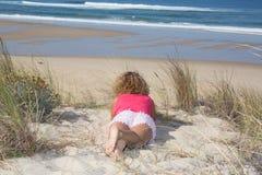 Mujer atractiva hermosa que miente en la playa y que mira al horizonte sobre el mar Foto de archivo libre de regalías