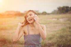 Mujer atractiva hermosa que se coloca que habla en el teléfono en el campo de hierba Fotografía de archivo