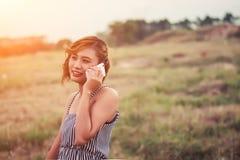 Mujer atractiva hermosa que se coloca que habla en el teléfono en el campo de hierba Foto de archivo