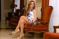 Mujer atractiva hermosa que se sienta en silla foto de archivo libre de regalías