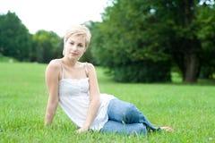 Mujer atractiva hermosa que sienta en gras verdes Imagenes de archivo