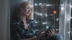 Mujer atractiva hermosa que usa Tablet PC y sentándose en el alféizar adornado con las guirnaldas almacen de metraje de vídeo