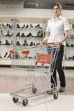 Mujer atractiva joven con el carro de compras Fotografía de archivo