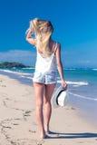 Mujer atractiva joven con el sombrero blanco que camina en la playa blanca de la arena una isla tropical de Bali en el día solead Fotos de archivo