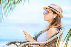 Mujer atractiva joven con los auriculares usando el teléfono en la playa Imágenes de archivo libres de regalías