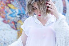 Mujer atractiva joven con los labios rojos en la presentación que camina blanca de la ropa casual en la calle fotografía de archivo libre de regalías