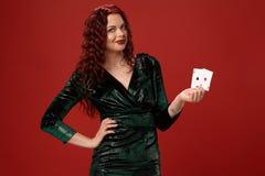 Mujer atractiva joven con un pelo rizado rojo que sostiene as, en un fondo rojo póker foto de archivo libre de regalías