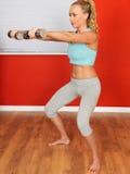 Mujer atractiva joven de la aptitud que usa las pesas de gimnasia que realizan un Sqaut Fotos de archivo libres de regalías