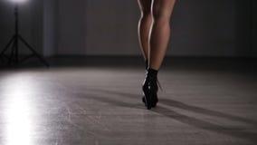 Mujer atractiva joven de la visión rara vestida en medias de la malla y calzoncillos de cuero negros La chica joven en tacones al almacen de video