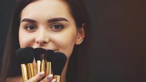 Mujer atractiva joven del artista de maquillaje que sostiene cepillos y que los efectúa en un estudio en un fondo negro Durante e almacen de metraje de vídeo