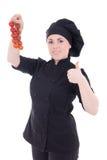 Mujer atractiva joven del cocinero en uniforme del negro con el aislante del tomate Foto de archivo libre de regalías