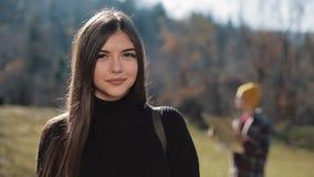 Mujer atractiva joven del retrato que mira en la cámara en las montañas Turista con un mapa en el fondo almacen de video